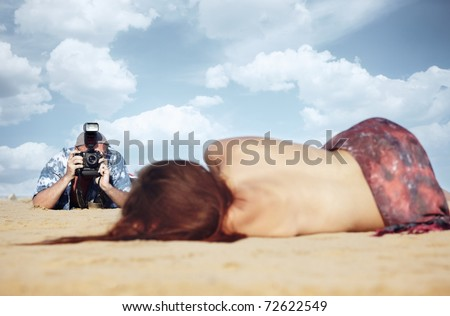 Male photographer outdoors holding modern camera and flash light and shooting model laying on sand - stock photo