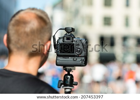 Male photographer preparing for photography assignment on a crowded street. - stock photo