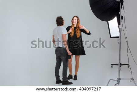 Male photographer speaking with female model in studio with equipments - stock photo