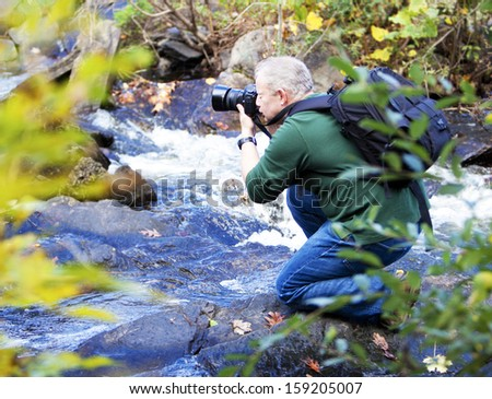 Male photographer taking photos in a waterfall in the Fall - stock photo