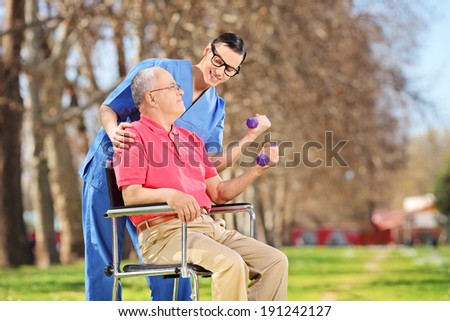 Male physiotherapist and a senior lifting dumbbells outdoors  - stock photo