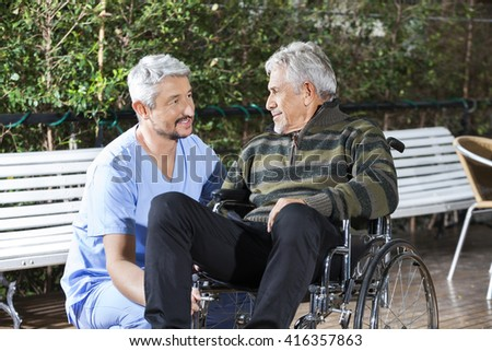 Male Physiotherapist Looking At Disabled Senior Man In Wheelchai - stock photo