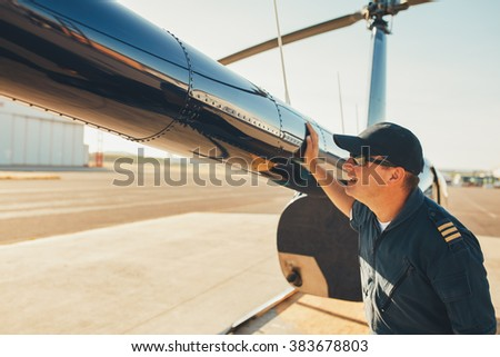 Male pilot checks the tail of helicopter before the flight. Mechanic checking helicopter before take off. - stock photo