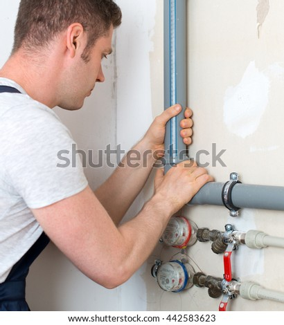 Male plumber assembling water pipes. - stock photo
