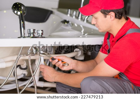 Male plumber fixing sink pipe in the bathroom. - stock photo