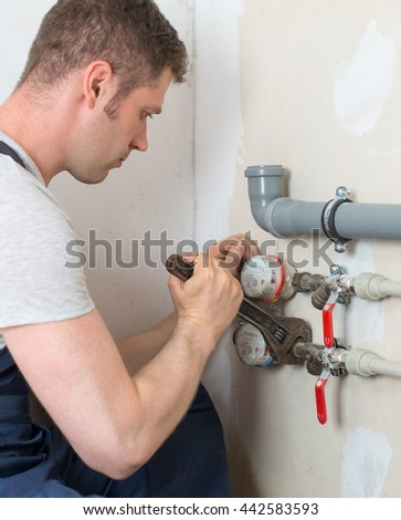Male plumber fixing water meter with adjustable wrench. - stock photo
