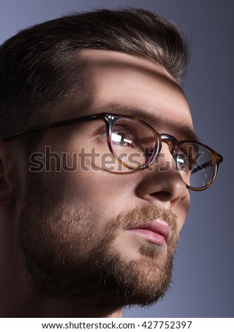 Male portrait closeup in harsh shadows. Stylish young man with glasses. Beard and mustache. Grey background - stock photo