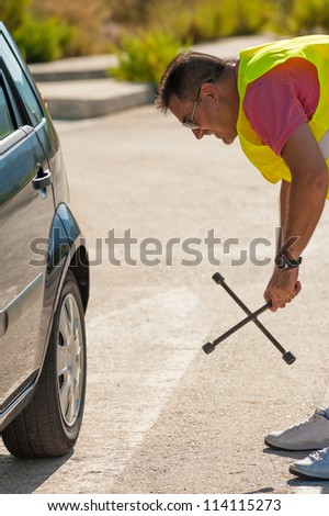 Male pretty unsure about how to handle a tool - stock photo