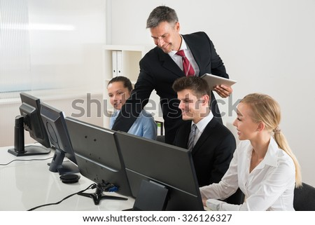 Male Professor Showing To Businesspeople On Computers At Desk - stock photo
