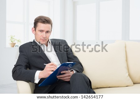 male psychologist  being ready to take notes  sitting on the couch - stock photo