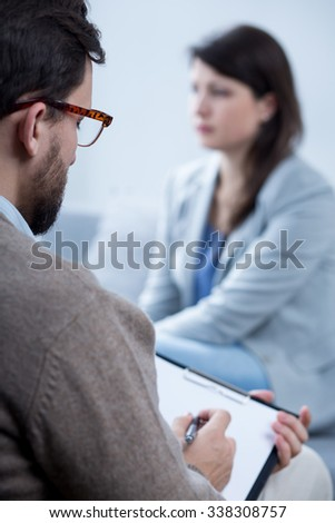 Male psychotherapist talking with young despair woman - stock photo