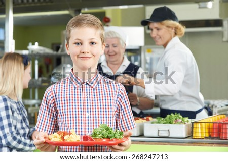 Male Pupil With Healthy Lunch In School Cafeteria - stock photo