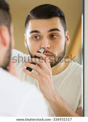 male remove hair from his nose and ears with trimmer - stock photo
