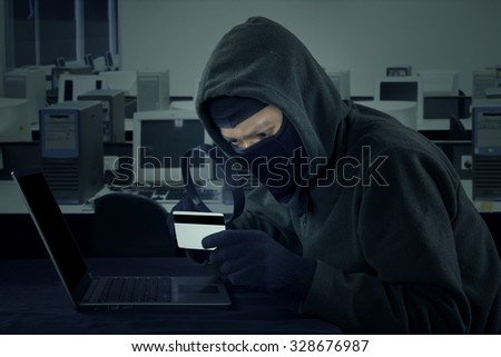 Male robber wearing mask and holding credit card, stealing the credit card information with notebook computer - stock photo