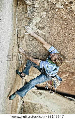 Male rock climber struggles for his next grip on a challenging ascent. - stock photo