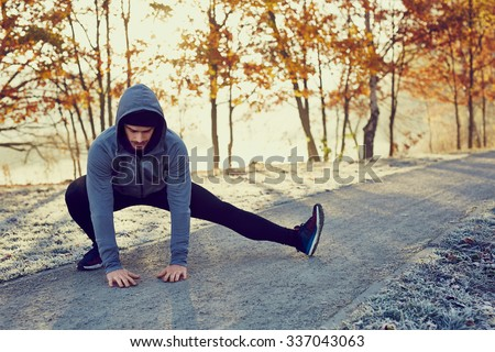 Male runner doing stretching exercise preparing for morning running workout in the park during sunny and cold fall - stock photo