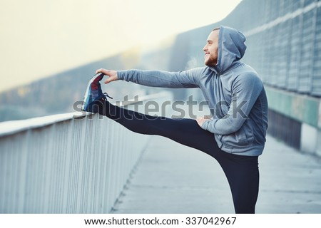 Male runner doing stretching exercise, preparing for morning workout in the park - stock photo