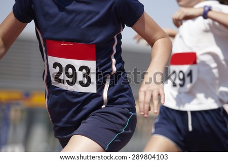 Male runner finalizing a race in a running track. Horizontal - stock photo