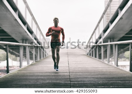 Male runner in the city. Caucasian Cheerful jogger male in his 20s - stock photo