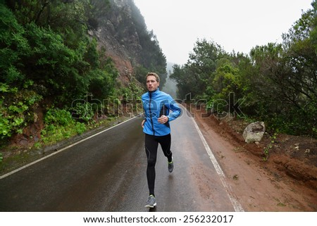Male runner jogging and running on road in rain in jacket and long tights. Fit fitness model man working out living healthy lifestyle training for marathon. Young caucasian model in his 20s. - stock photo