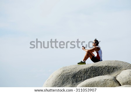 Male runner listening to music in headphones while sitting on rock cliff against sky copy space background for your text message or advertising, weary mature jogger resting after workout jog outdoors - stock photo