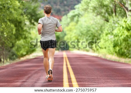 Male runner running on road training for fitness. Man doing jogging workout run outside in summer in nature. Athlete in running shoes and shorts working out for marathon. - stock photo