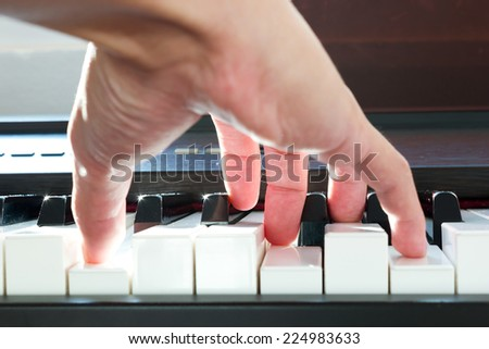 Male's hand playing piano taken from low angle point. - stock photo