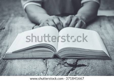 male's hand with open book on old wooden table - stock photo