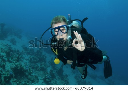 Male scuba diver gives OK sign in clear blue water - stock photo