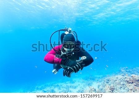 Male scuba diver swimming under water - stock photo