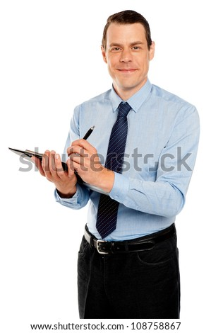 Male secretary taking down notes from boss on notepad looking at camera - stock photo