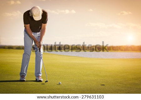 Male senior golf player putting on green at beautiful sunset, with empty copyspace. - stock photo