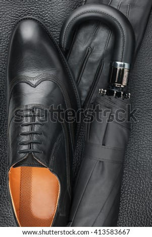 Male set of fashion accessories, shoes, umbrella, gloves lying on the natural skin - stock photo