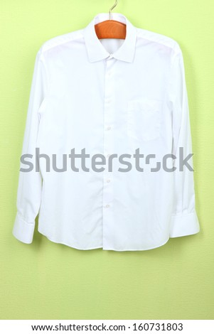 Male shirt on wooden hanger on wall background - stock photo