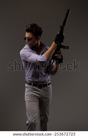 Male shooter with automatic rifle facing right. - stock photo