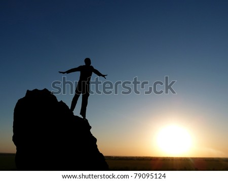 male silhouette on top of the mountain reaches for the sun - stock photo