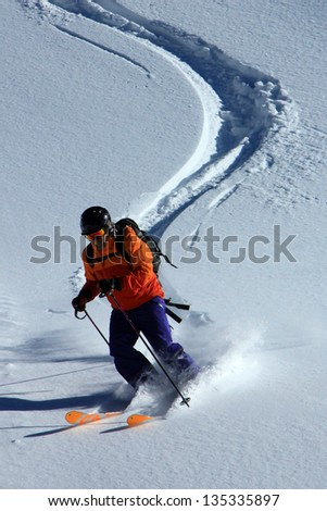 Male skier carving in fresh powder snow. - stock photo