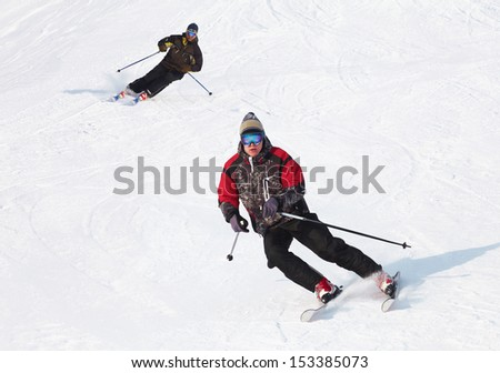 Male skier turning in deep powder with mountains valley's  - stock photo