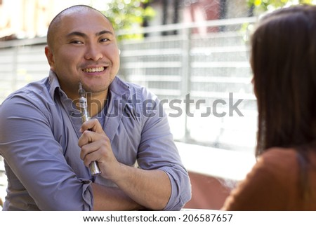 male smoker on a date using modern e-cigarette vaporizer - stock photo