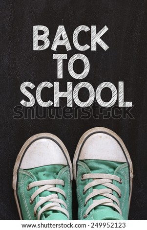 Male sneakers and back to school. Male sneakers on the asphalt road with drawn back to school - stock photo