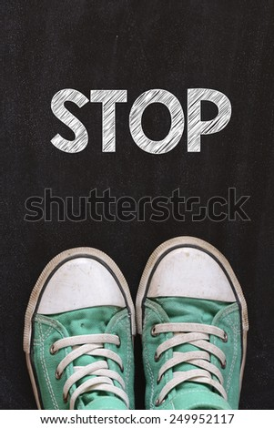 Male sneakers and word stop. Male sneakers on the asphalt road with drawn word stop - stock photo