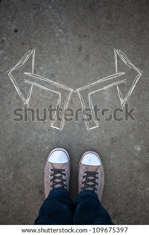 Male sneakers on the asphalt road with drawn arrows pointing to two directions. Youth guidance, student guide, advisory concept. Making decisions and making choices. - stock photo