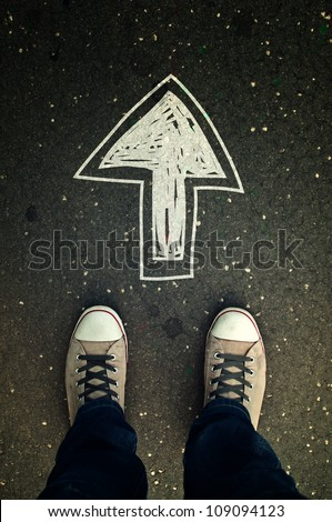 Male sneakers on the asphalt road with drawn direction arrow as Youth education, youth guidance, student guide, consultation, advisory concept, top view - stock photo