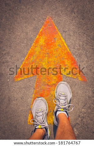 Male sneakers on the asphalt road with drawn direction arrow. Youth education, youth guidance, student guide, consultation, advisory concept. - stock photo