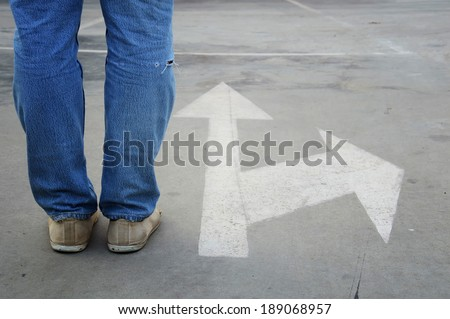male sneakers with jeans on the tarmac road with white direction arrow, concept of making decision at the crossroad - stock photo