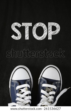 Male sneakers with stop word. Male sneakers with stop word on the back background - stock photo