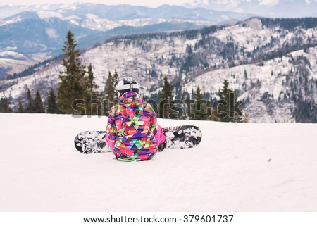 Male snowboarder looks into the distance on snowy mountain - stock photo