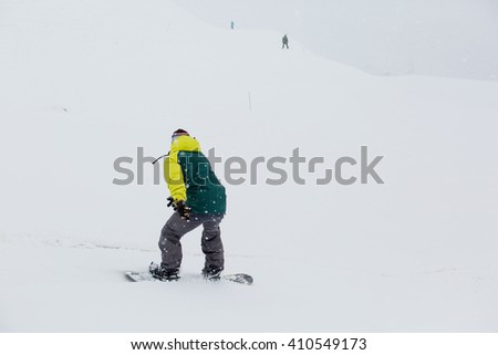Male snowboarder snowboarding on fresh snow on ski slope on Sunny winter day in the ski resort in Georgia - stock photo