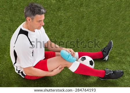 Male Soccer Player Icing Knee With Ice Pack On Field - stock photo