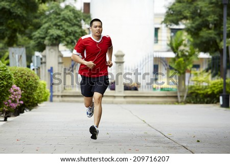 Male sport fitness model with sweat listening to music with earphones in the park - stock photo